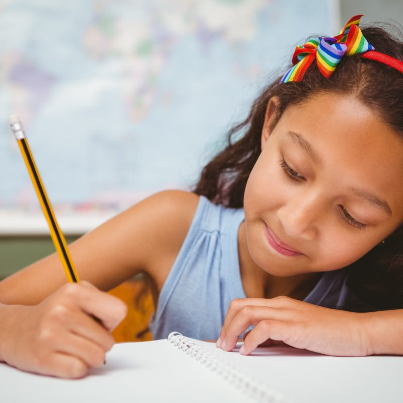 Little girl in a classroom writing in her book with a world map behind her