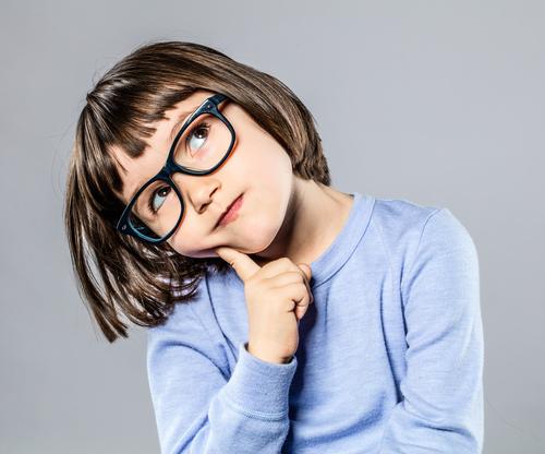 Little brunette girl with glasses thinking